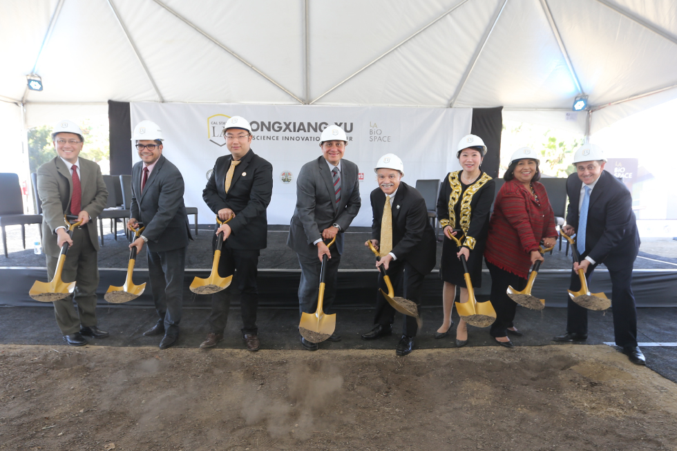 Group of administrators and partners shoveling dirt at the BioSpace ground breaking event